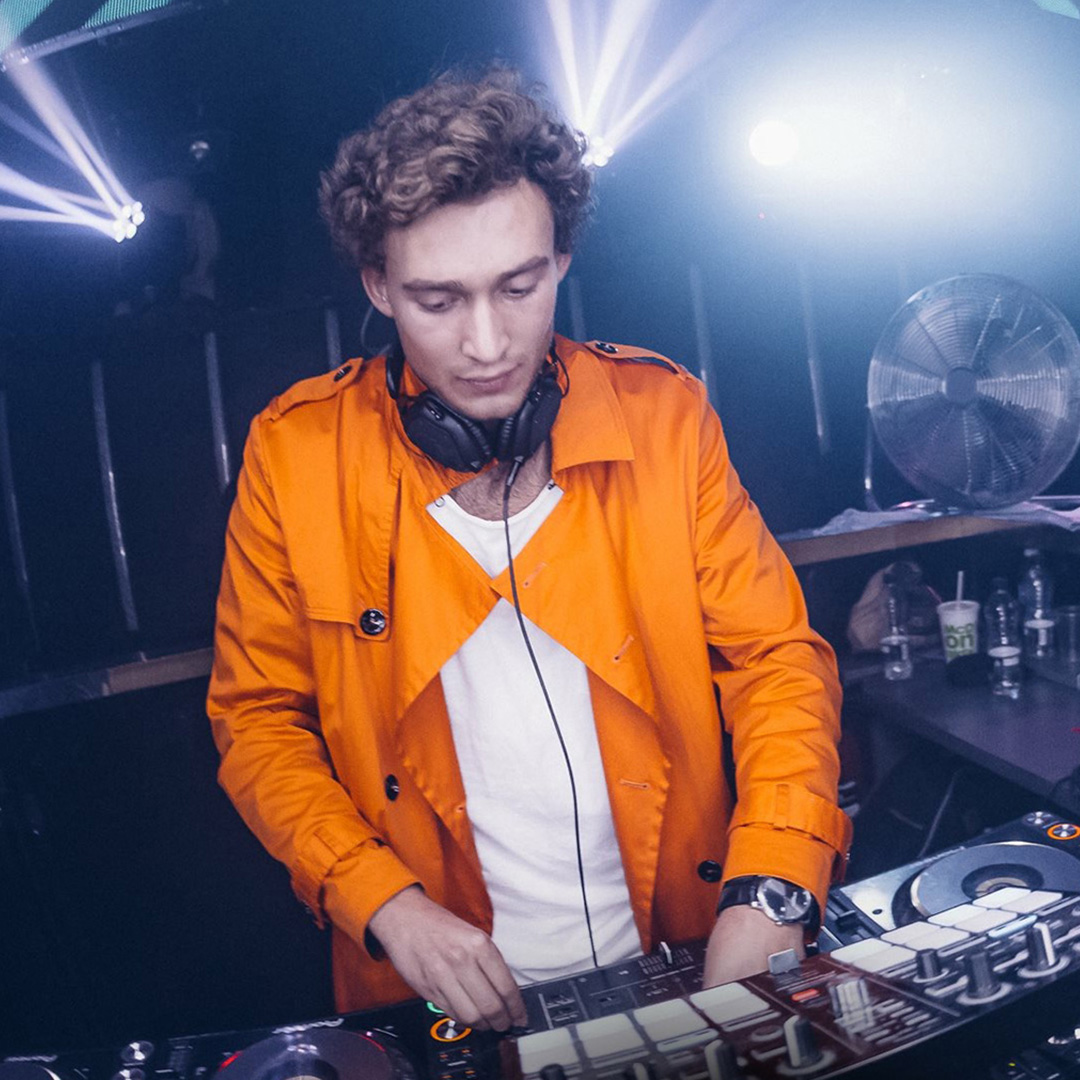 CharLeon behind DJ decks orange jacket